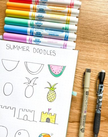 Summer doodles in notebook with Crayola markers and a black pen laying on counter