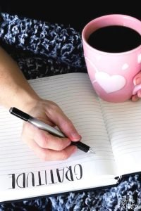 Woman writing in gratitude log while drinking coffee in a pink mug