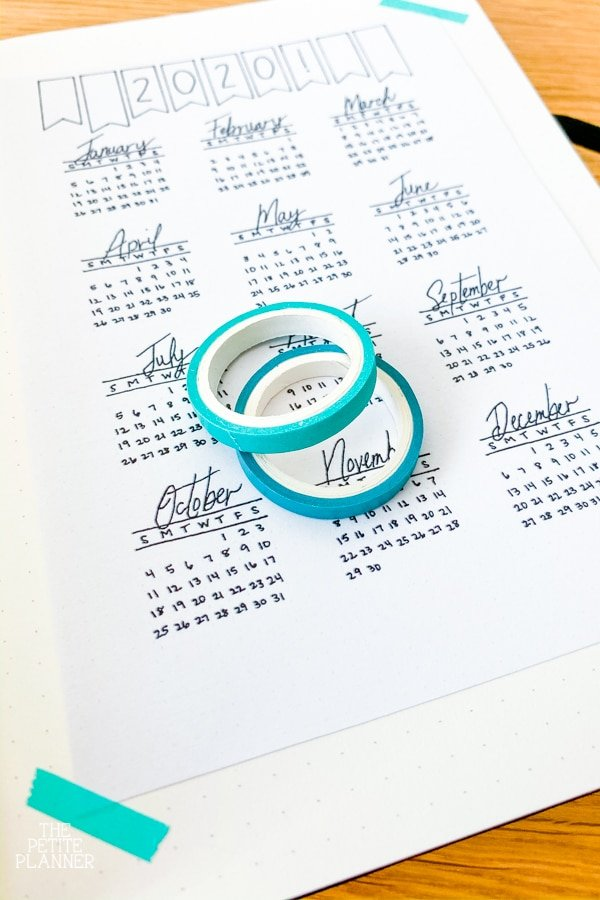 Rolls of teal washi tape sitting on top of a 2020 tear at a glance calendar page in a journal
