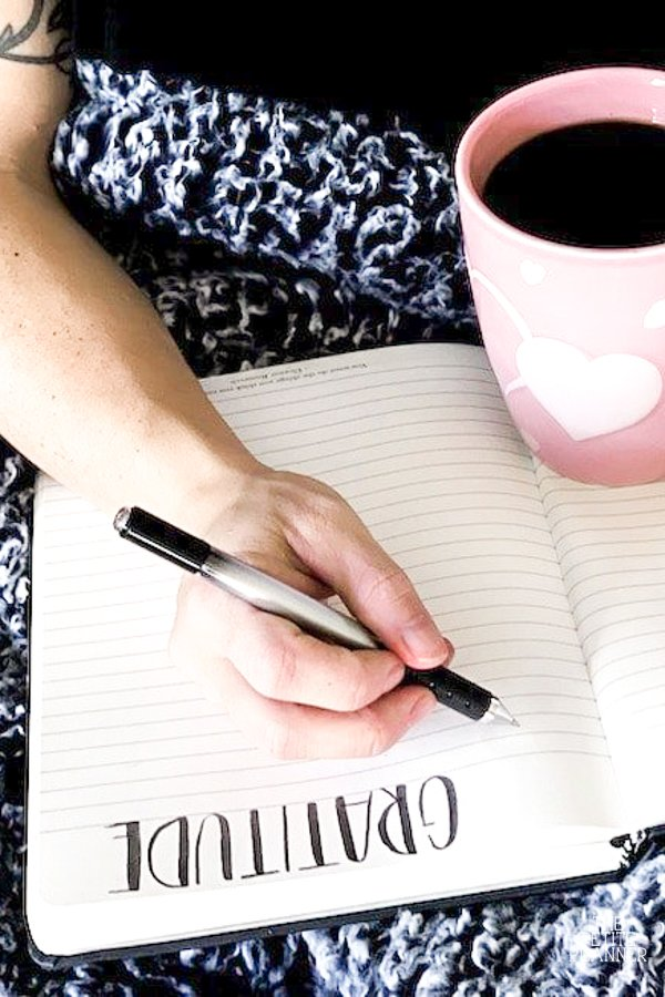 Woman sitting with gray blanket, gratitude journal, and a cup of coffee