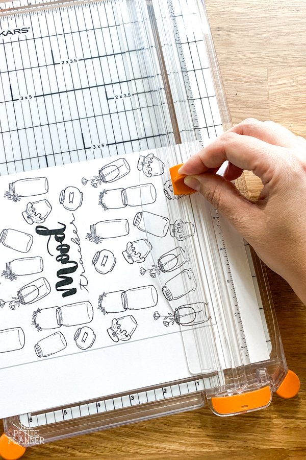Using a paper cutter to trim a mood tracker printable edges