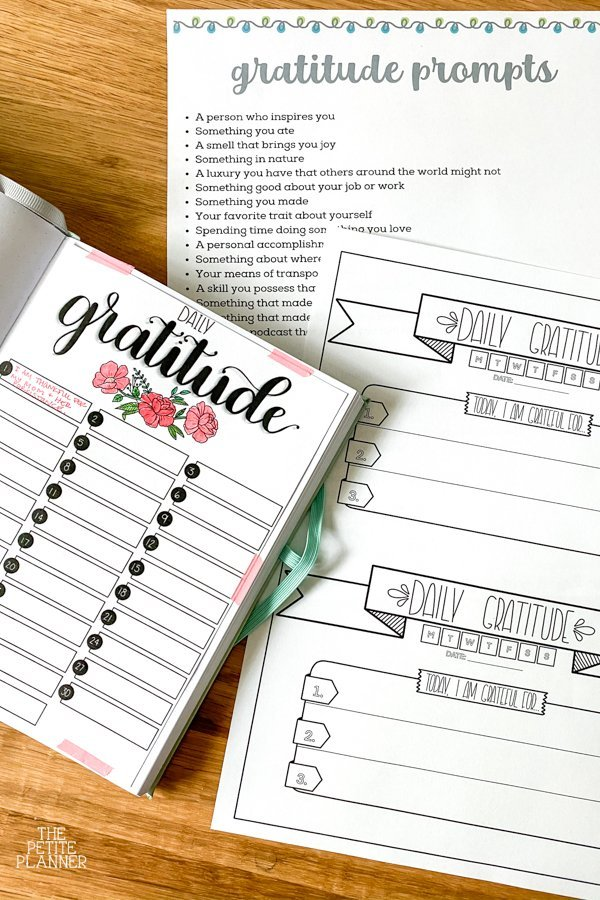 Gratitude journal in a bullet journal notebook and a printable gratitude log on a counter