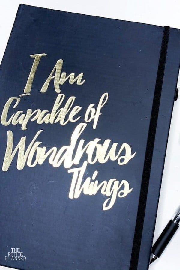 "Notebook that says ""I am Capable of Wondrous Things"" on black cover"