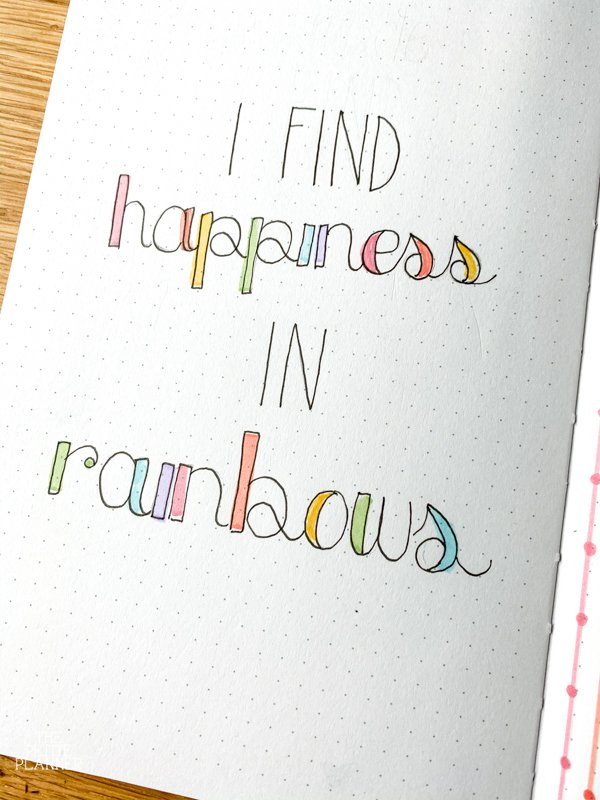 I Find Happiness in Rainbows quote in dotted notebook