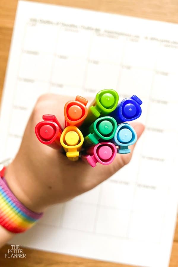 Hand holding pens with caps of different colors of the rainbow