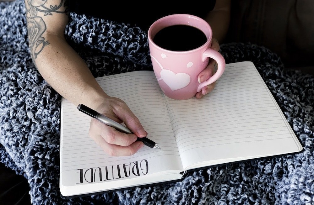 Woman writing in gratitude log with pink coffee cup