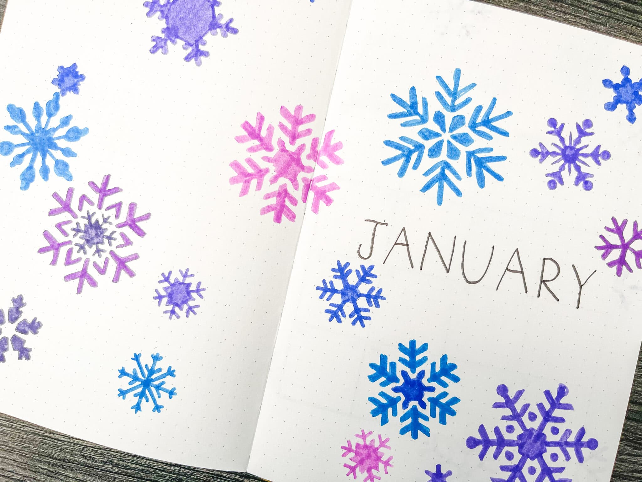 Blue and purple snowflake doodles in bullet journal
