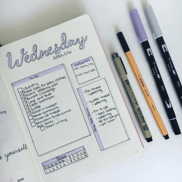 Bullet journal weekly page with black and purple lettering