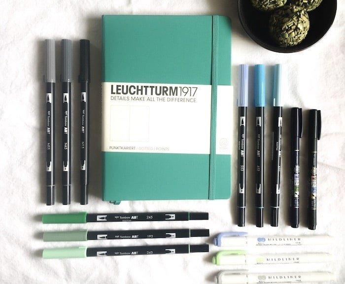 Leuchtturm Bullet Journal with brush pens next to it