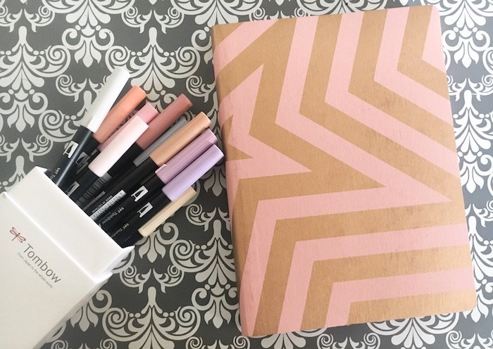Small bullet journal notebook with a box of Tombow markers